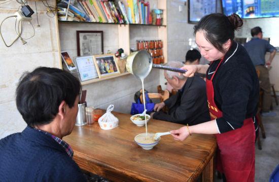 图为:早餐店老板娘正在为顾客冲泡豆浆。 王刚 摄