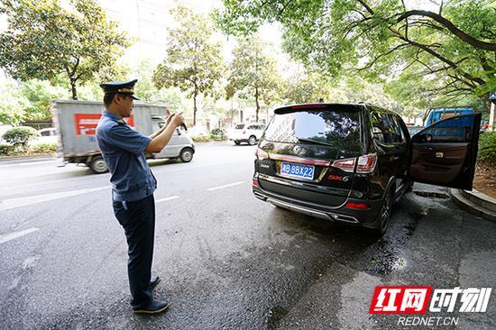 执法人员给涉嫌违法车辆牌照取证。