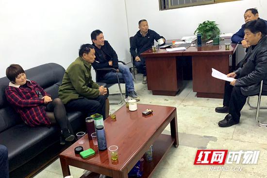 罗伟军(右三)生前在办公室与居民商谈拆迁事宜。(资料图)