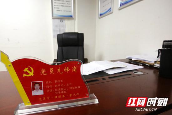 罗伟军生前办公桌上的座位牌上写着他的承诺。