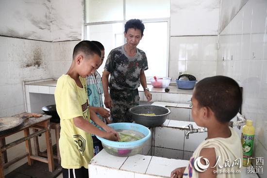 图为梁志雄教学生做家务。韦世仙 摄影