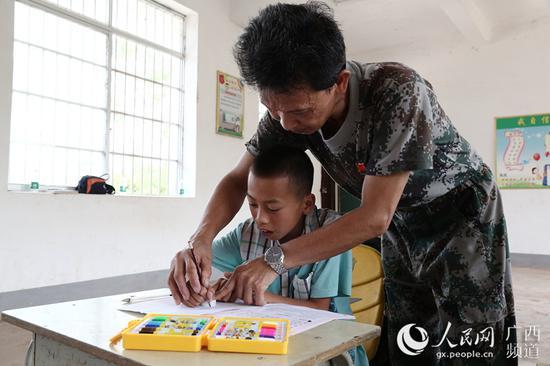 图为梁志雄在教学生写字。韦世仙 摄影