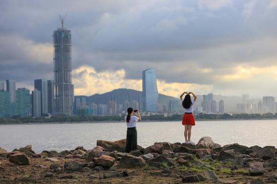 ▲游客站在深圳湾公园的海滨礁石上,与朝霞合影。