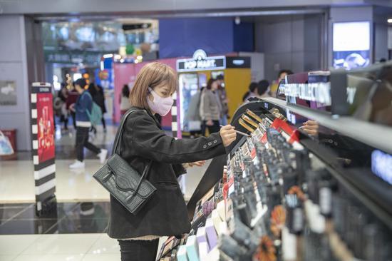 2月15日,在重庆市江北区观音桥商圈一家商场内,市民在美妆店选购心仪的美妆用品。新华社记者 黄伟 摄