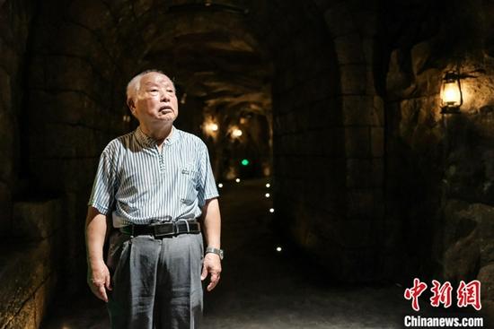 """图为8月11日,粟远奎在重庆大轰炸""""六·五""""隧道惨案遗址防空隧道内。中新社记者 何蓬磊 摄"""