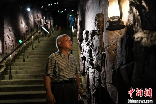 """图为8月11日,粟远奎在重庆大轰炸""""六·五""""隧道惨案遗址防空隧道内悼念。中新社记者 何蓬磊 摄"""