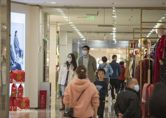 2月15日,在重庆市江北区观音桥商圈一商场内,市民在服装层选购衣服。新华社记者 黄伟 摄