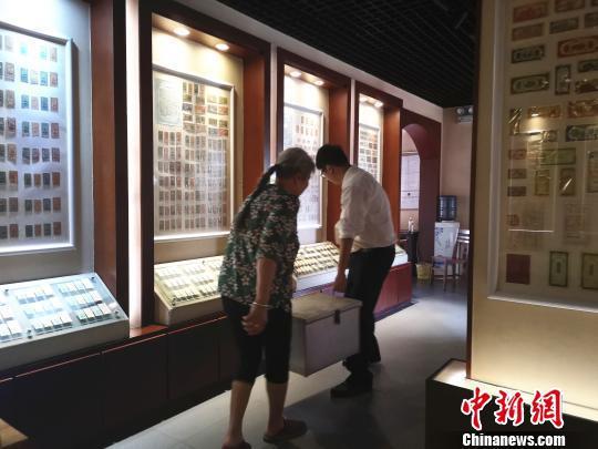 李广智与母亲王老四抬着藏品,送往别地展出。 朱柳融 摄