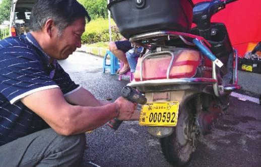 6月5日上午,长沙市开福区青竹湖街道太阳山社区前坪,一辆电动车正在安装防盗备案号牌。记者丁鹏志摄