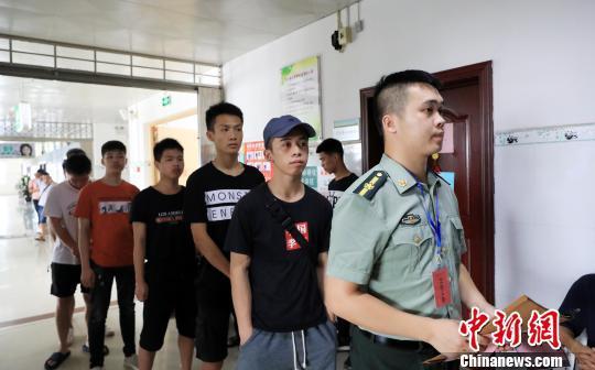 一名专武干部带领适龄大学生参加体检。 谭凯兴 摄