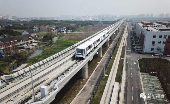 上海,2018年3月23日,地铁列车行驶在上海首条无人驾驶APM线路——浦江线上(无人机航拍)。 新华社记者丁汀摄