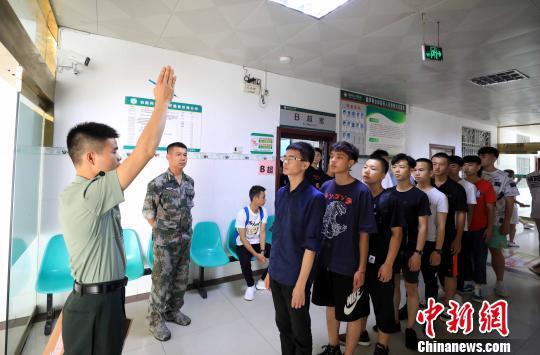一名专武干部指挥大学生参加体检。 谭凯兴 摄