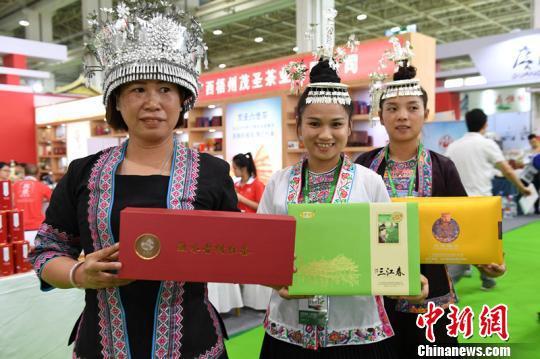 图为身着民族服饰的广西茶商现场宣传桂茶。 李爱平 摄