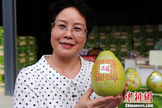 李东兴在展示绘制有文创图案的文旦柚。 蒋雪林 摄
