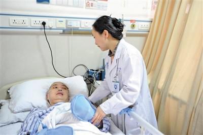 李霞绯在病床前悉心照顾丈夫。