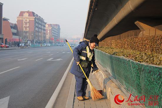 2018年2月16日(正月初一)天津环卫工于春萍在黑牛城道和解放南路交口清扫道路,路边见不到扫之不尽的鞭炮皮。张静淇/摄