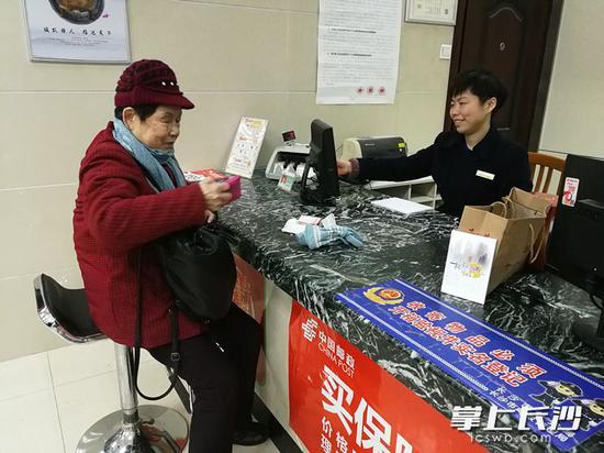 周娭毑走到湖南邮政八一支行,缴了300元电费。 长沙晚报记者 伍玲 摄