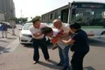 唐山:老人遇车流难通行 公交小伙背老人过马路