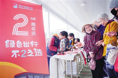 在南宁BRT举办的2周年庆宣传活动中,民主路小学书法班的学生在BRT通道内挥毫泼墨,为市民书写春联。 本报记者叶子榕 摄