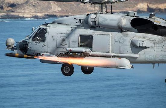 """图为正在发射""""海尔法""""反坦克/船舰导弹的MH-60S舰载直升机。"""