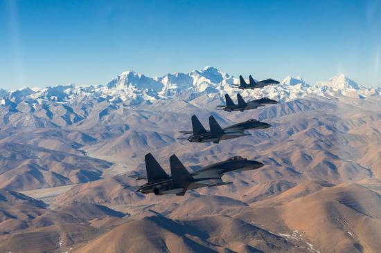 东部战区空军某旅歼-11B战机编队飞行在雪域高原上空。