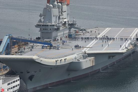 5月10日,舰员们在国产航母上排成一排,清理甲板(图片来源:东方ic)