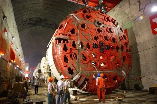 2014年6月,全断面隧道掘进机进行组装调试   承受巨大载荷和强烈温升   掘进机主轴承工作环境非常恶劣,要承受高速旋转、巨大载荷和强烈温升。   掘进机工作的地质具有未知和突变的特点,加上刀盘滚刀破岩时的突变载荷,使得主轴承必须承受住持续、突变和各个方向的载荷。洛阳轴承研究所有限公司李云峰博士说。   以直径15米掘进机为例,整机重4500吨,主轴承所在主机重2800吨,轴承连接的前部刀盘就达520吨;掘进机动力来自28组千斤顶,最大推力达22500吨,掘进速度最大每分钟5厘米。要传送这样大