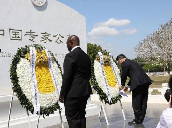 中共中间对外笼络部部长宋涛(右)向纪念碑敬献花圈