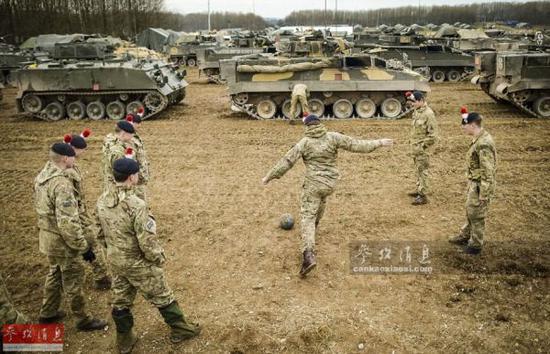 """资料图:隶属于英国陆军第一""""皇家燧发枪""""步兵团第一营的士兵们正在演习间隙踢足球休整。"""
