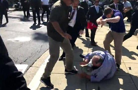 一名手持土耳其国旗的穿西装男子猛踢一名反对埃尔多安的抗议者