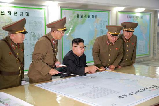 朝中社15日公布金正恩(中)听取关岛包围射击方案的照片。路透社