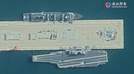 图说:10月21日的卫星照片显示,呼伦湖舰与辽宁舰共同停泊在某军港。