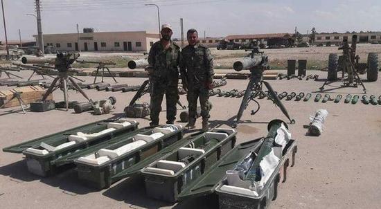 图为叙利亚政府军士兵在缴获的武器中间庆祝东卡拉蒙的解放。