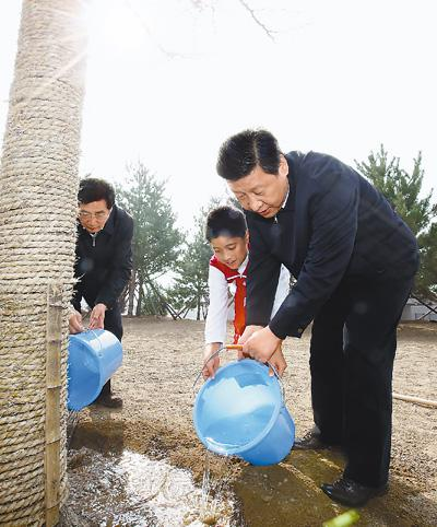 2013年4月2日,习近平同少先队员一起给?#36213;?#19979;的银杏树浇水。新华社记者 鞠鹏摄