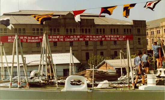 """图注:停泊在上海港的""""考文垂""""号驱逐舰,岸边建筑外墙上挂有欢迎标语横幅"""