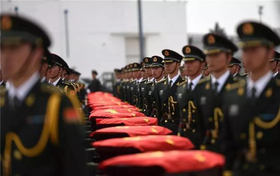 2014年3月28日,礼兵护卫着中国人民志愿军烈士遗骸棺椁。新华社记者 李钢 摄