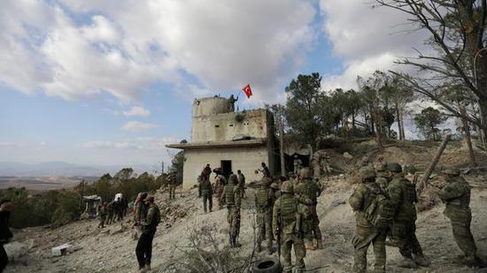 图注:土耳其部队在叙Afrin东北部巴巴亚山上举起一面旗帜。