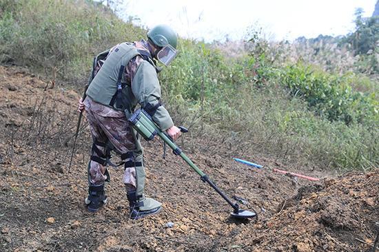 扫雷战士拿着仪器正在地面探测。