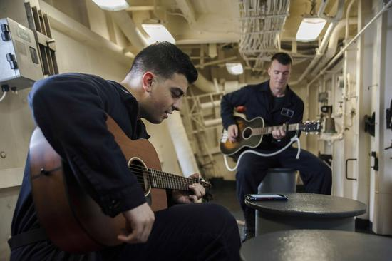 """1月1日,""""圣迭戈""""号航行南海时,两名水兵在舰上悠闲弹吉他"""