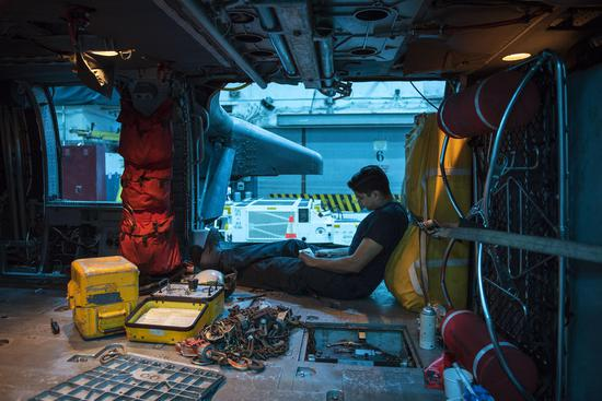 2月6日,一位机械师正在对MH-60S直升机进行例行检查。