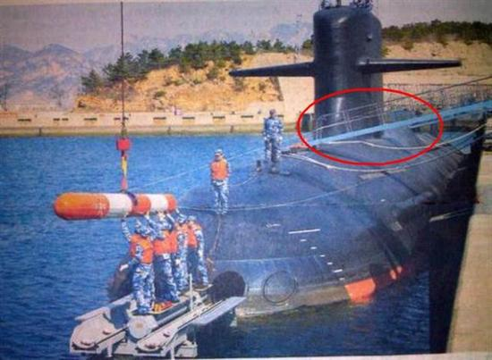 图片:093B核潜艇从鱼雷口装填训练鱼雷,注意后部的龟背和指挥塔围壳修形。