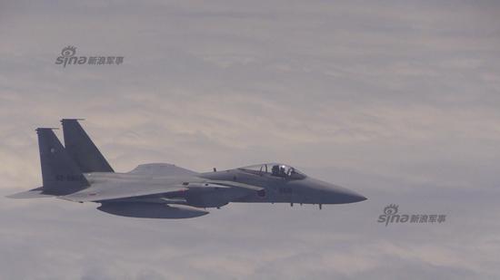 """两架日本F-15JH战机均挂载AAM-4格斗导弹,其中编号815 F-15J战机还调整机身向我军机展示了其机翼下挂载的武器,该动作是国际标准的警告动作,意思是""""你已进入我领空,马上离开,我携带有武器""""!"""