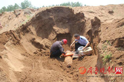 图为排爆专家和民警在沙塘内小心翼翼地安置航弹。