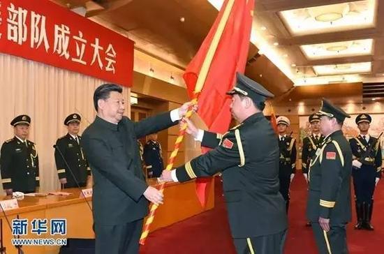 2015年12月31日,中国人民解放军陆军领导机构、中国人民解放军火箭军、中国人民解放军战略支援部队成立大会在北京八一大楼隆重举行。习近平向陆军、火箭军、战略支援部队授予军旗并致训词。这是习近平将军旗郑重授予陆军司令员李作成、政治委员刘雷。新华社记者 李刚 摄