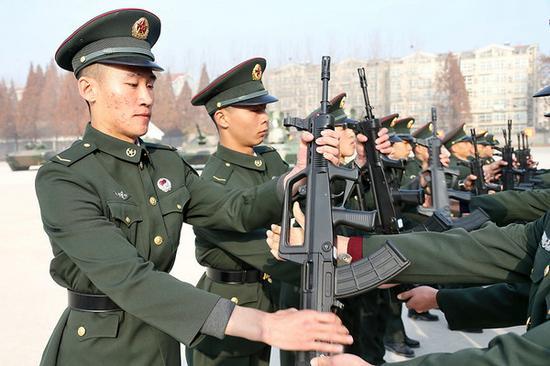 新兵接过前辈的枪,立志在军营中建功立业。