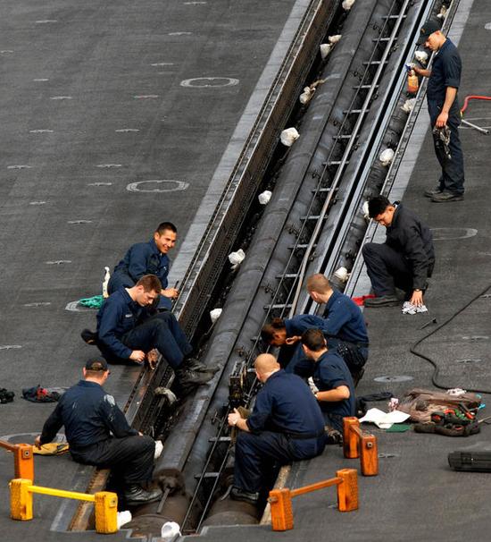 """蒸汽弹射器可以说是美国""""尼米兹""""级的作战核心力量,图为CVN-72""""林肯""""号正在进行弹射器维护工作"""