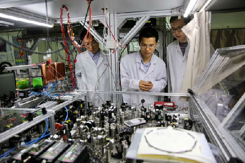 资料图:世界首台超越早期经典计算机的光量子计算机在中国诞生。2017年5月3日,中国科学技术大学陆朝阳教授(中)和学生们在中科院量子信息和量子科技创新研究院上海实验室检查光量子计算机的运行情况。新华社记者 金立旺 摄