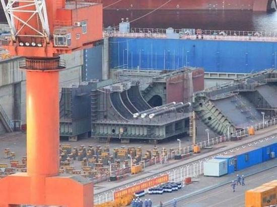 原文配图:大连造船厂一辑新照片中,在已抽干的船坞里出现的疑似新航母的组件。