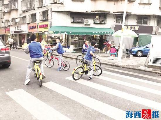 小朋友骑着小黄车在马路上行驶。记者陈小斌摄