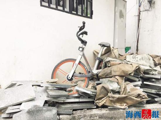 """官任路上,一辆共享单车""""可怜""""地被掩埋在建筑材料中。"""